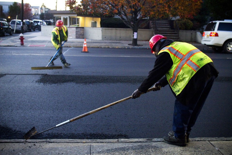 Two workers in safety gear using hand tools to smooth pavement.